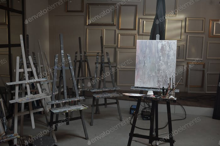 Interior of contemporary arts school or studio with unfinished picture on easel