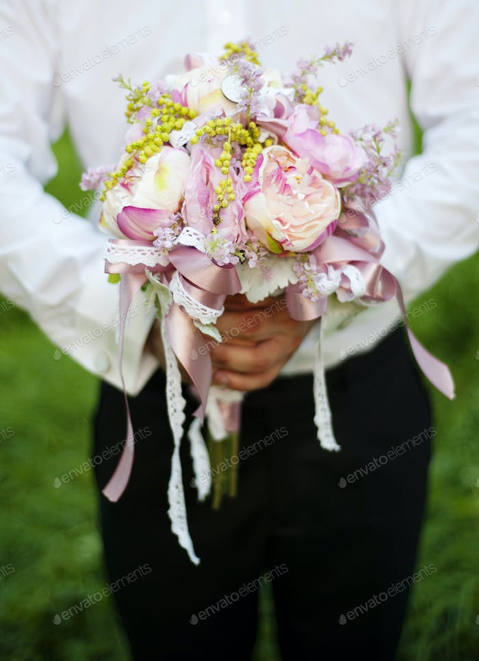 Groom holding bouquet for bride