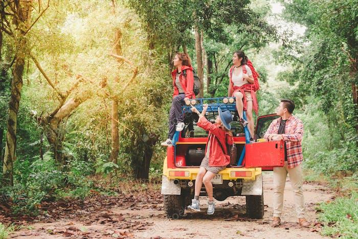 Glückliche asiatische junge Reisende mit Allradantrieb Auto abseits der Straße im Wald.