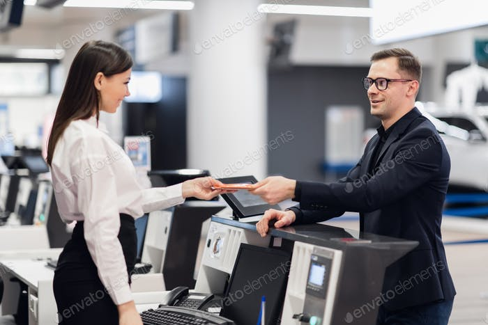 Friendly woman staff taking passport from passenger at airport check in desk