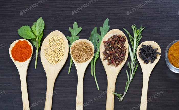 Colorful spices and wooden cutlery