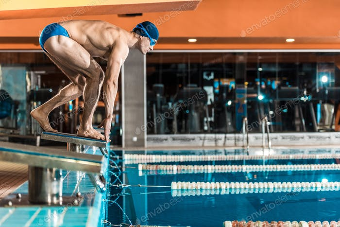 swimmer standing on diving board ready to jump into competition swimming pool