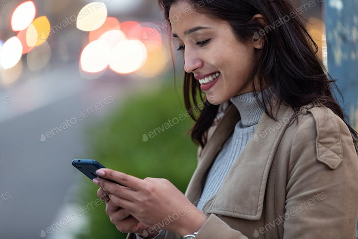 Pretty young woman using her smartphone while standing in the street.