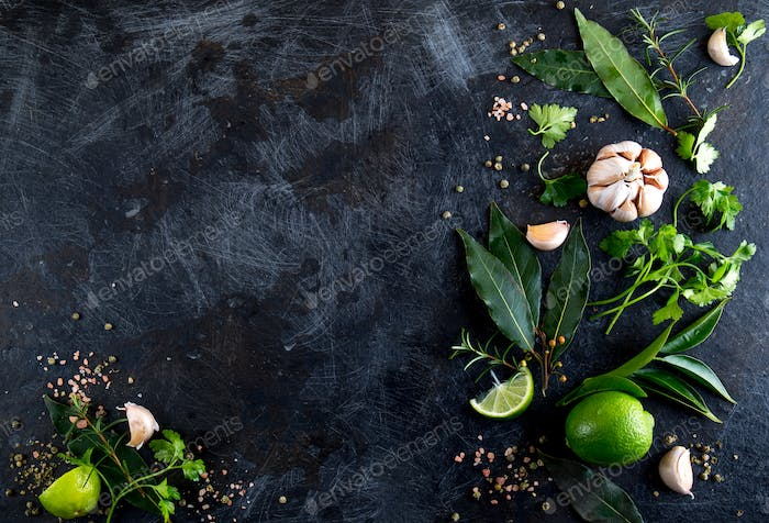 Fresh herbs and spices on black background. - garlic, laurel, lime, rosemary, parsley pepper