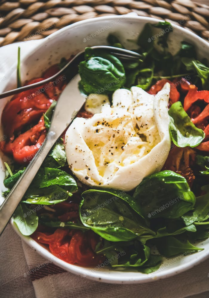 Italian salad with Buratta cheese in white bowl, close-up