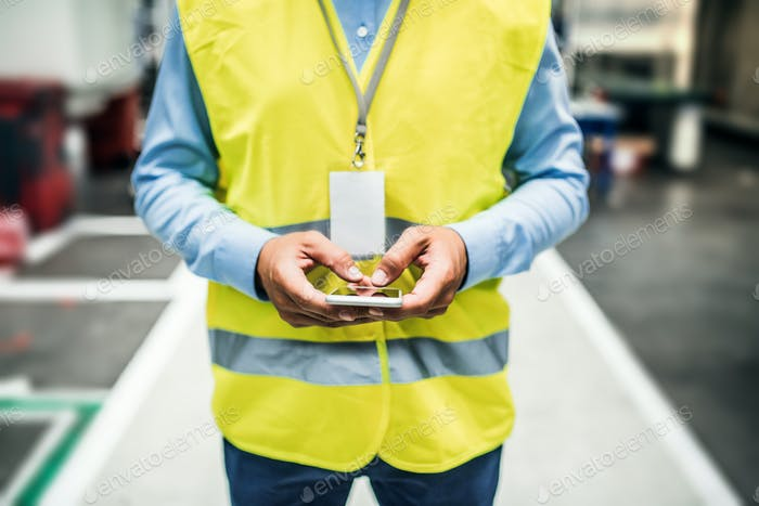 An unrecognizable industrial man engineer with name tag in a factory, using smartphone.