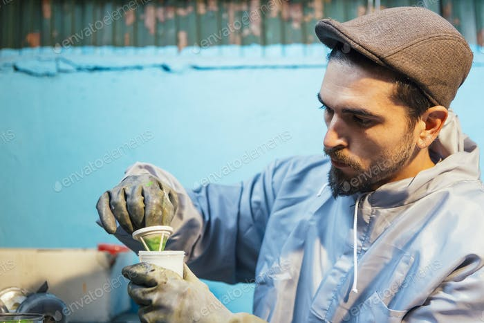 Man preparing tool with green color