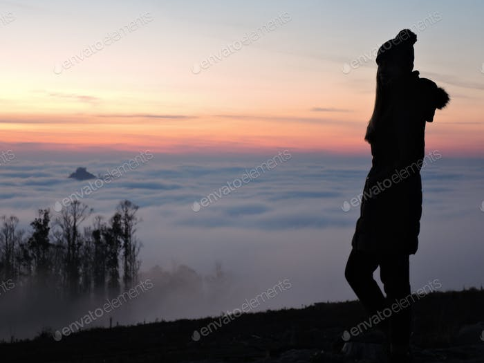 Lone female hiker contemplating the clouds from the top of a mountain
