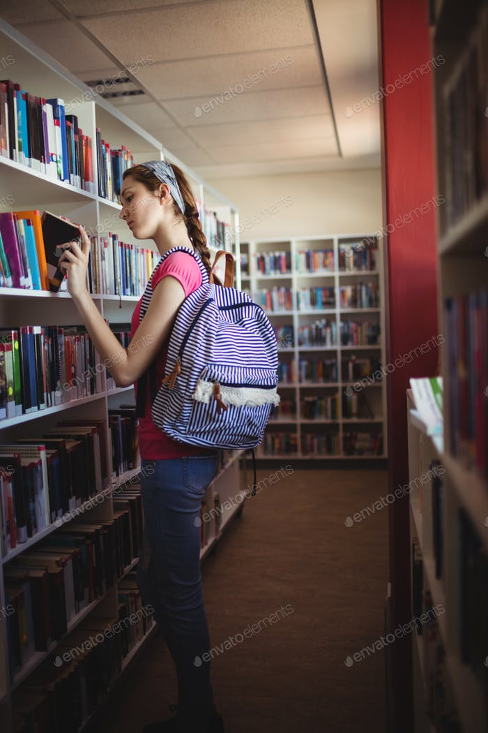 Schoolgirl selecting book in library