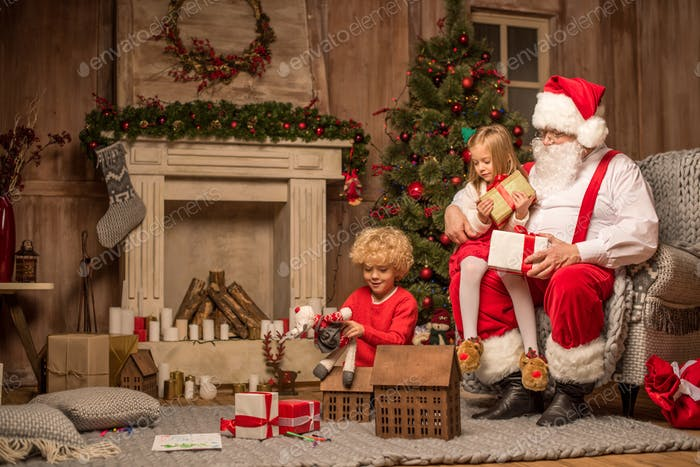 Santa Claus and children sitting with gift boxes by fireplace