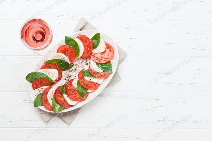 Delicious italian caprese salad and wine glass