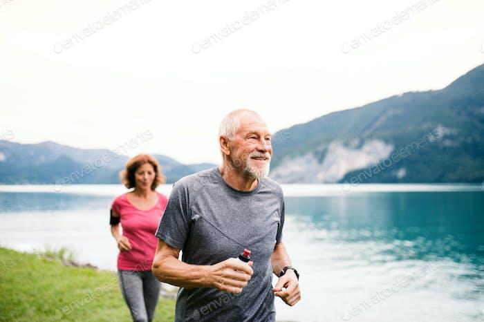Seniorenpaar mit Smartphone läuft am See in der Natur.