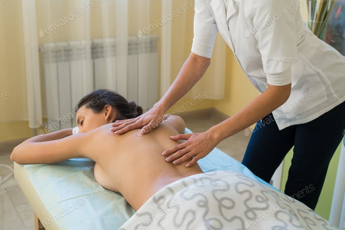 Portrait of a relaxed woman lying on massage table in health spa