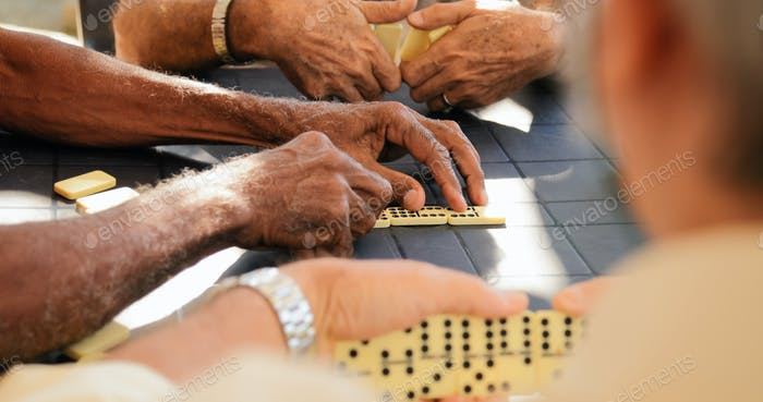 Retired Old Men Playing Domino Game With Friends