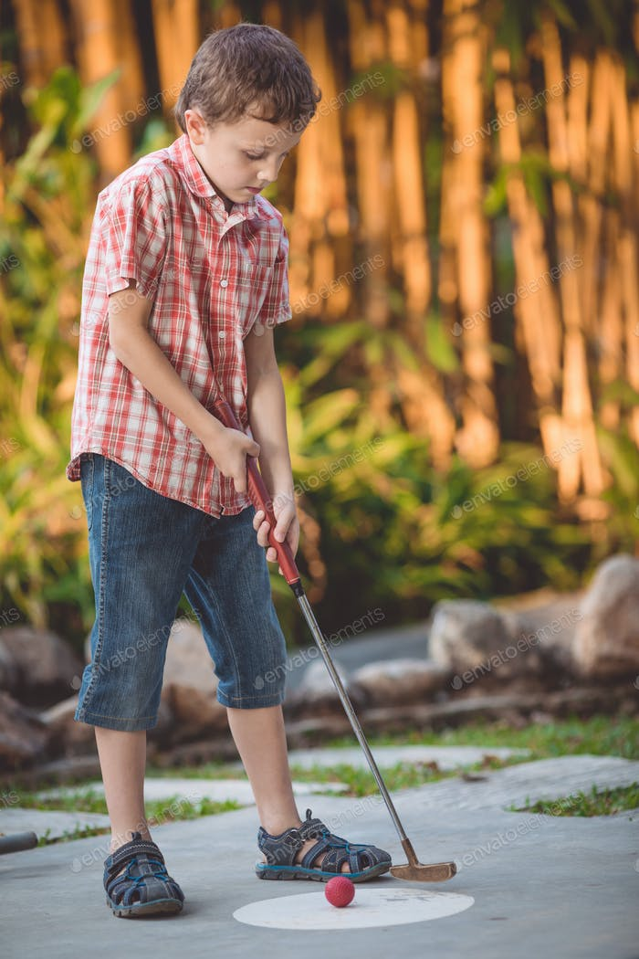 Happy little boy  playing mini golf.