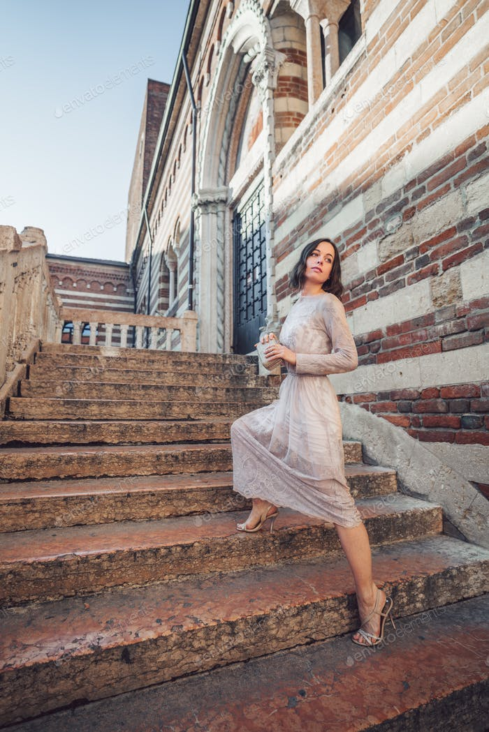 Young girl in a beautiful dress on the stairs
