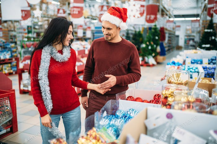 Young couple chooses christmas tree toys in shop