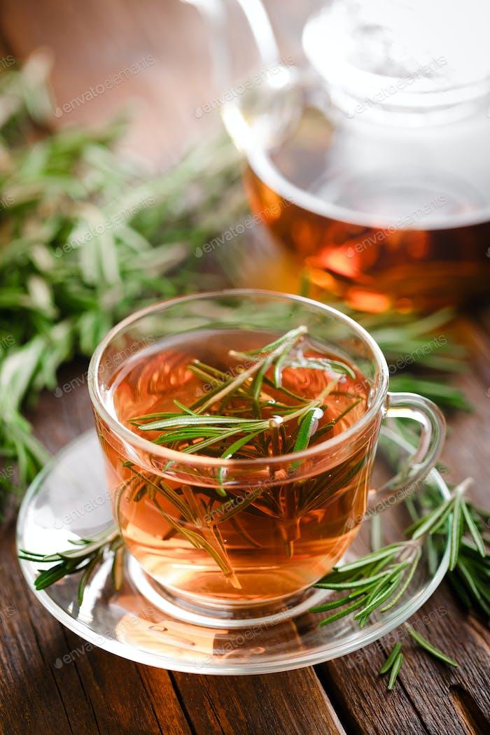 Rosemary tea in glass tea cup on rustic wooden table closeup. Herbal vitamin tea.