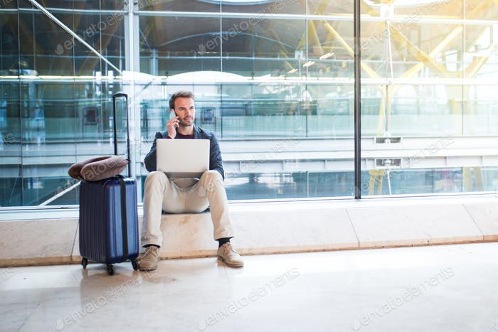man sitting at the airport using laptop and mobile phone next to