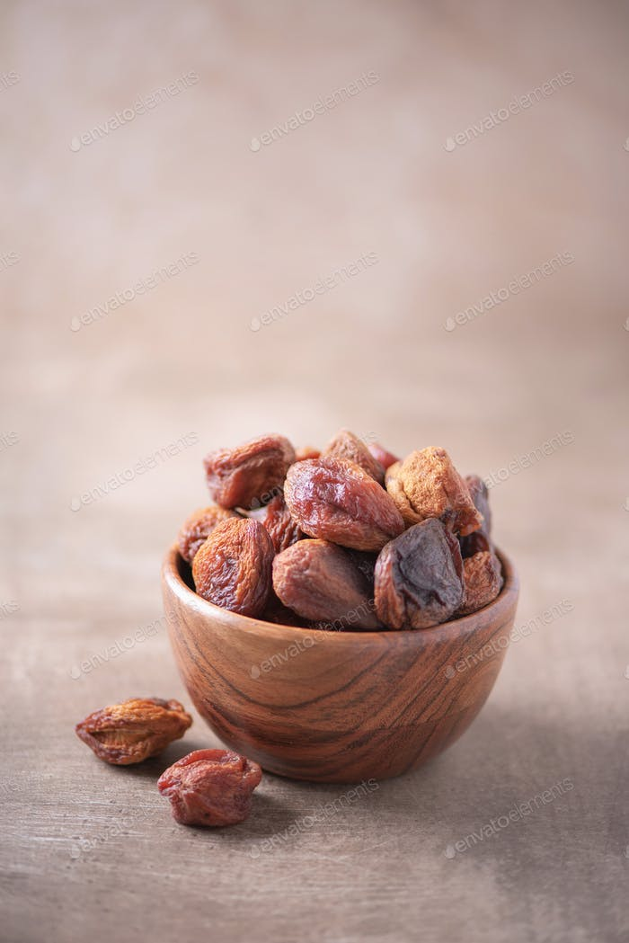 Homemade dried apricots in wooden bowl on wood textured background. Copy space. Superfood, vegan