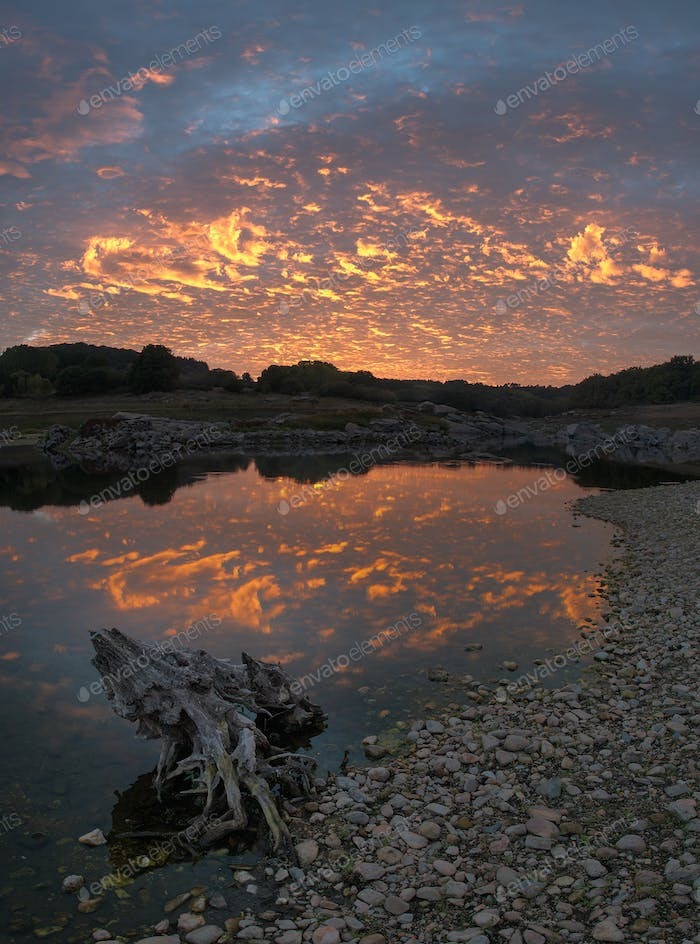 Orange cirrocumulus at sunset over the river