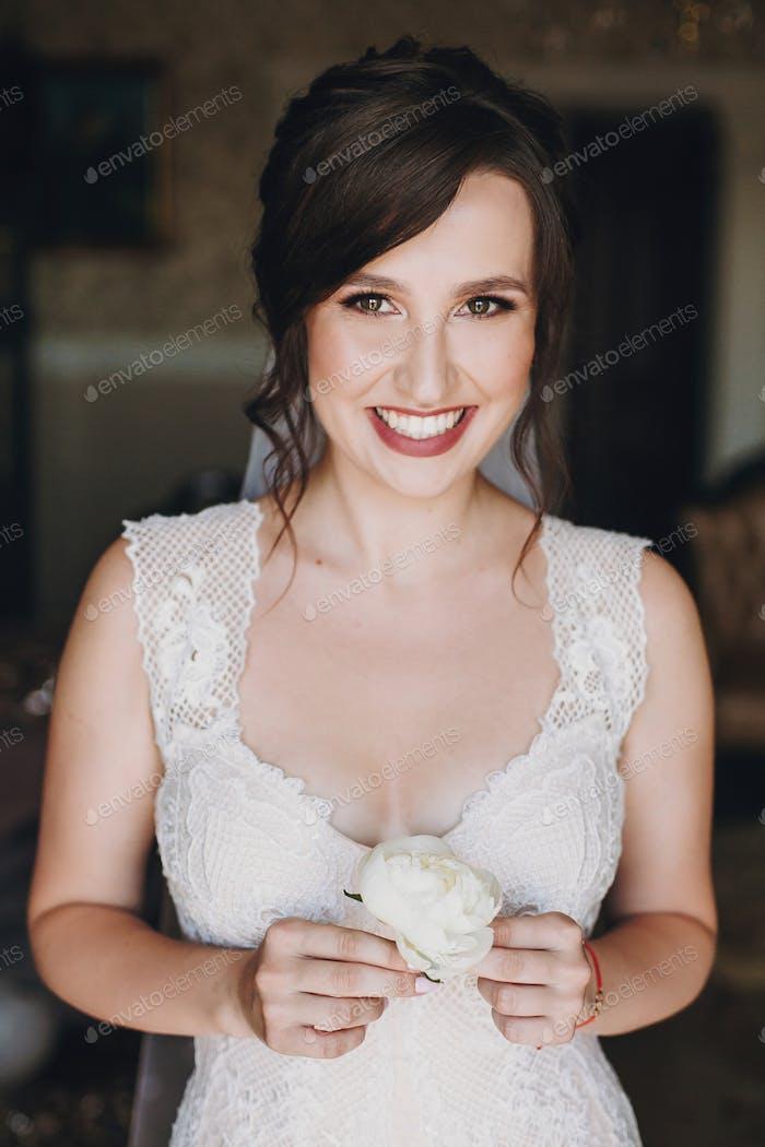 Wunderschöne Braut in erstaunlichen Kleid hält weiße Pfingstrose Boutonniere in den Händen
