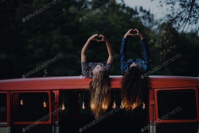 Zwei Freundinnen in der Dämmerung draußen auf einem Roadtrip durch die Landschaft, Spaß haben.