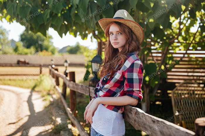 Portrait of pretty redhead cowgirl leaning on the ranch fence