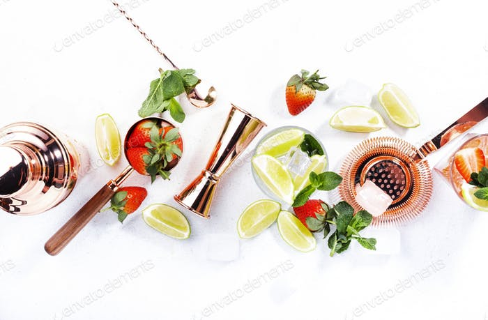 Fresh Mojito cocktail set with lime, mint, strawberry and ice in glass on white