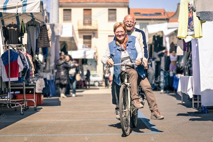 Happy senior couple having fun with bicycle at flea market