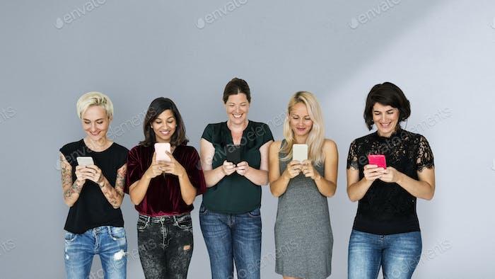 Gruppe von Frauen, die auf ihren Handys schreiben