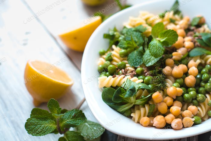 Pasta with peas and mint on the white wooden table horizontal