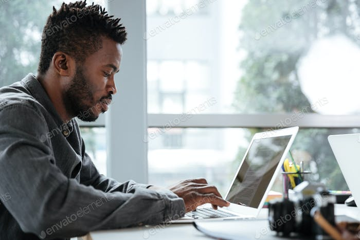 Handsome thinking serious young man sitting in office coworking