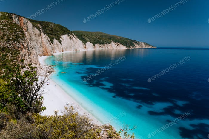 Panoramic view of Fteri beach, blue lagoon with rocky coastline, Kefalonia, Greece. Calm clear blue