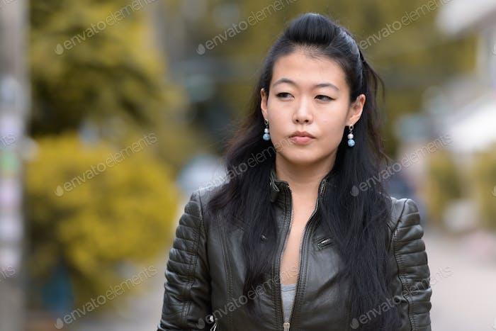Gesicht der schönen asiatischen rebellischen Frau denken im freien
