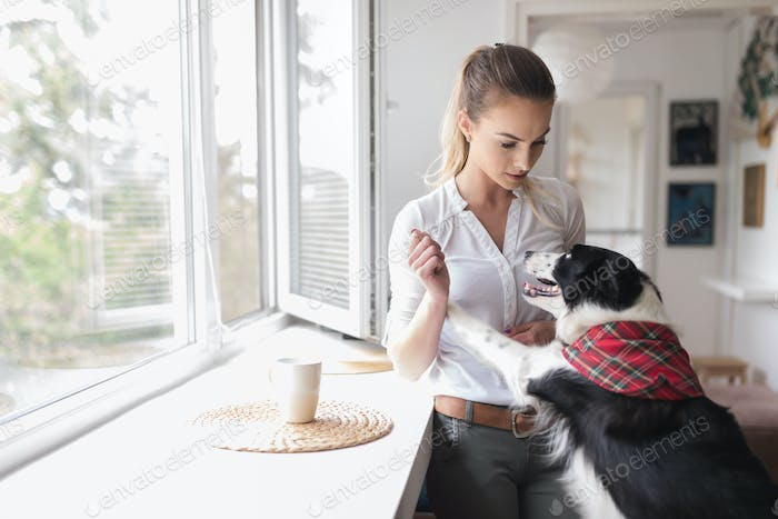 Beautiful woman playing at home with her happy dog