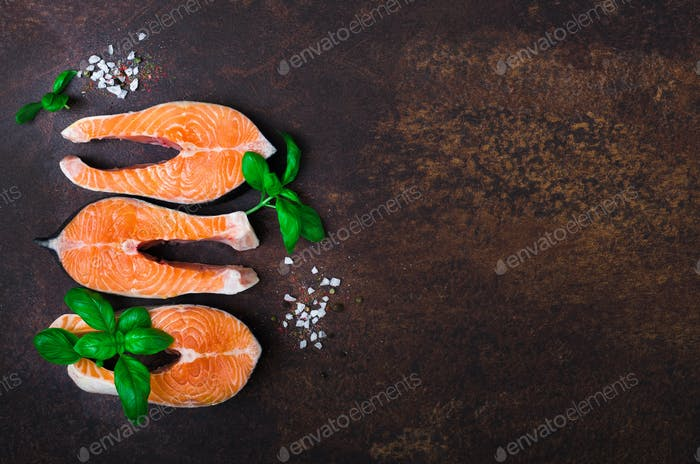 Raw fresh salmon steak with vegetables. Ingredients for cooking on brown background. Space for text