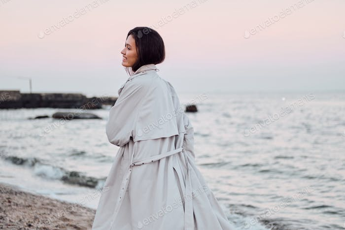 Back view of pretty stylish Asian girl in trench coat happily walking by the sea