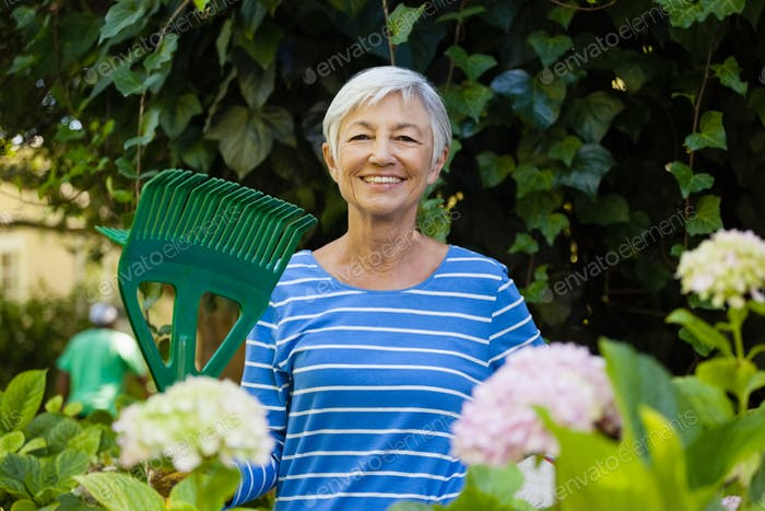 Porträt der lächelnden Seniorin mit Rechen inmitten von Pflanzen