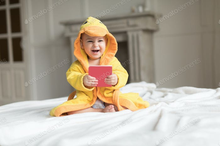 Happy baby boy in yellow robe posing on bed