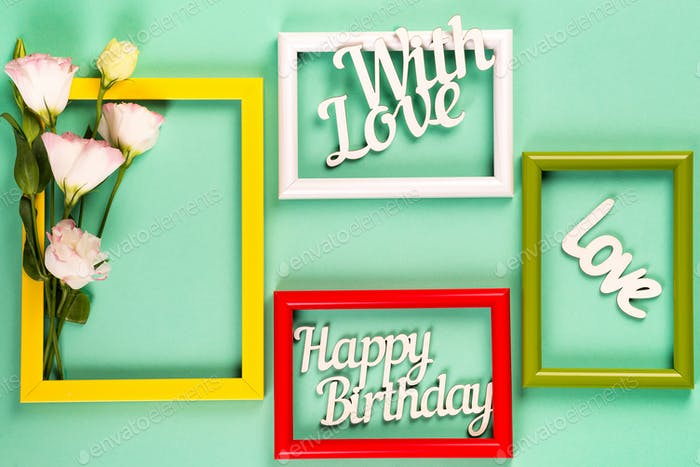 Bunte Bilder- oder Bilderrahmen mit Blumen und Buchstaben auf einem grünen Papierhintergrund. Kopierbereich