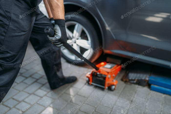 Auto mechanic jacks the car in tire service
