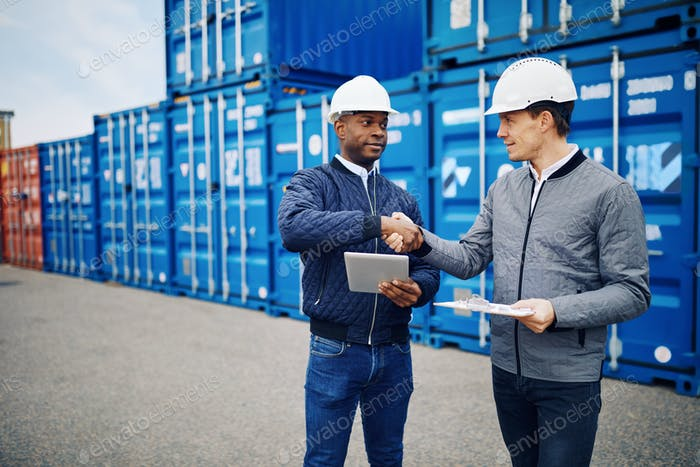 Engineers shaking hands while standing in a shipping container yard