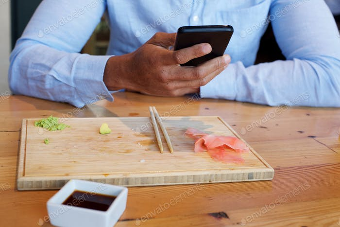 businessman finished with food holding mobile phone