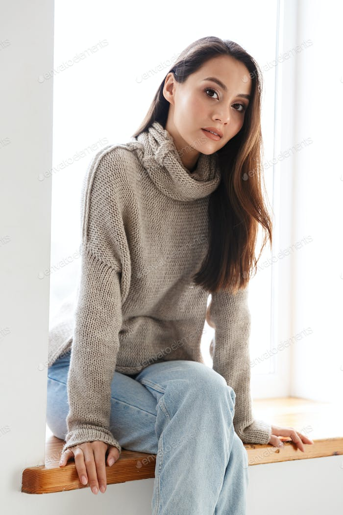 Image of beautiful asian woman looking at camera while sitting on window sill