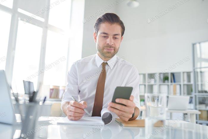 Молодой предприниматель прокрутки в смартфоне