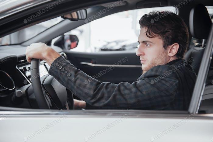 Bereit für Probefahrt. Porträt eines gut aussehenden Geschäftsmann Auto fahren