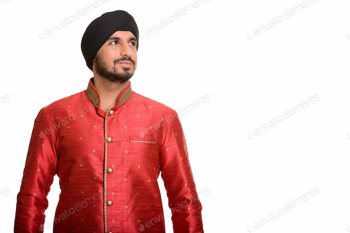 Young handsome Indian Sikh thinking while wearing traditional cl