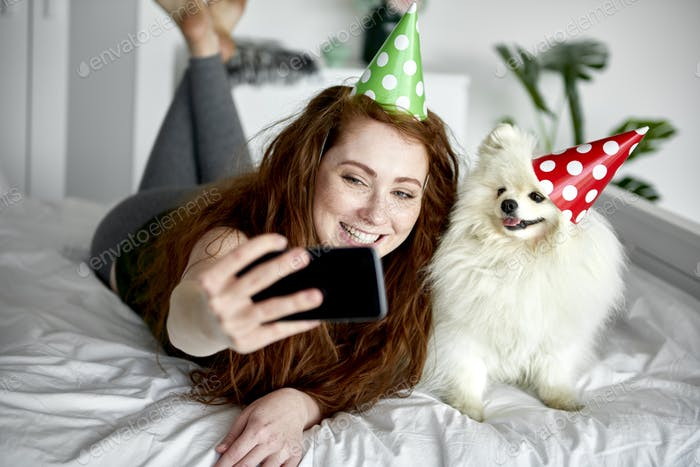 Woman taking birthday selfie with her pet dog