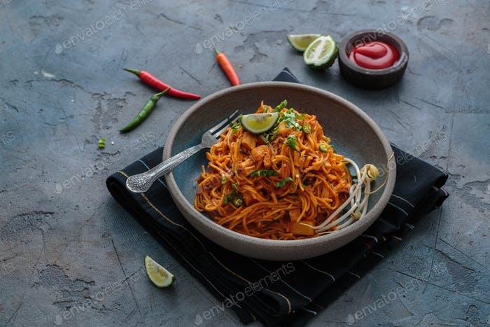 Indian mee goreng, spicy fried noodles in a plate, Singaporean and Malaysian cuisine copy space